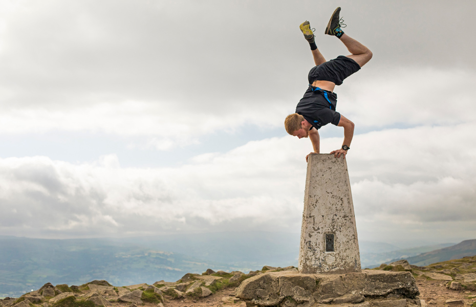 photo of man doing stunt on sugar loaf mountain in wales